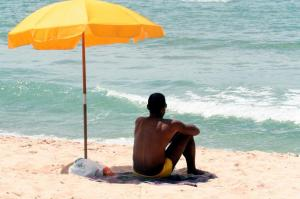 man_sitting_under_beach_umbrella-300x235